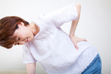 腰痛に悩む女性のイメージ